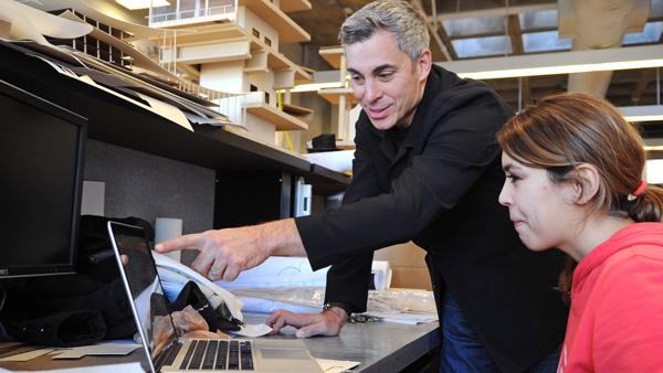 Design professor helping architecture student with computer model