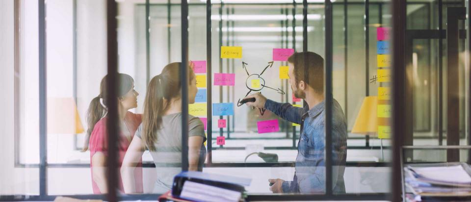 Group of casual business people working in front of glass wall using notes papers post it.
