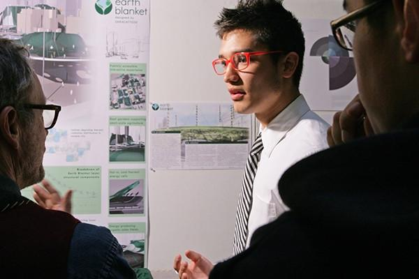 Male student with red glasses presenting design project to professors